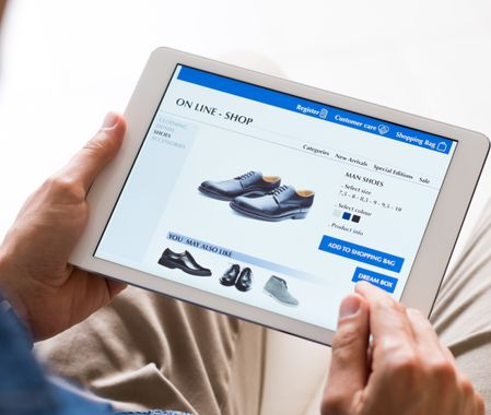 Man looking at various shoes options over internet through digital tablet