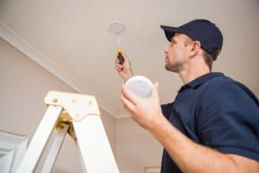 A worker installing a smoke detector.
