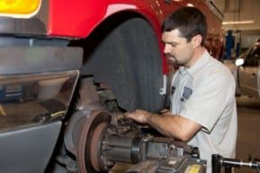 Mechanic checks tractor trailer truck brakes after New Jersey truck accident.