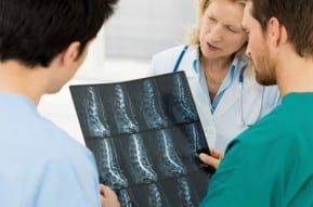 A team of doctors reviews an xray of a New Jersey spinal cord injury
