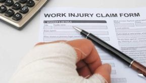Bandaged hand next to a pen and a Work Injury Claim Form