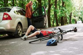 Bicycle and silver colored car accident on the road