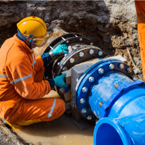 a worker fixing an old big drink water pipes