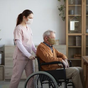 young female nurse taking care of an old man