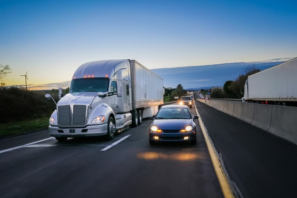 truck driving next to car