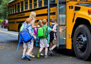 children walking into a school bus