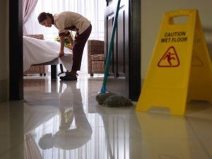 Maid cleaning up a hotel room with a 'wet floor' sign to avoid premises liability on Long Island.