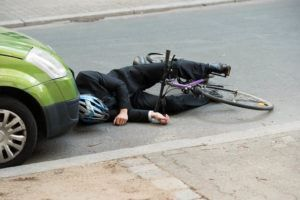 cyclist laying on the road in front a car after a collision