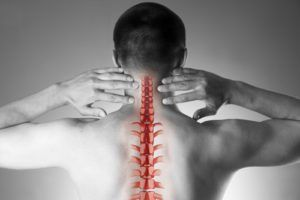 Spine pain, man with backache and ache in the neck, black and white photo with red backbone on gray background