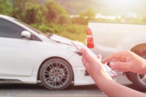 Man using smartphone at roadside after car accident