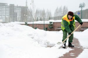 man clearing ice and snow
