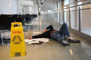injured man laying on the floor due to a wet floor slip and fall