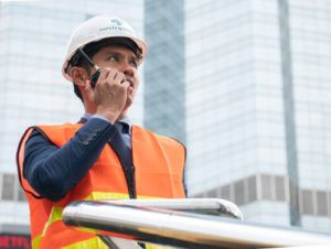 construction engineer coordinating through handheld transceiver