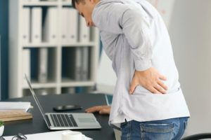man suffering from chronic back pain as a result of a slip and fall accident