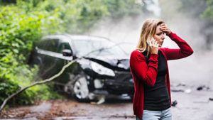 woman using cellphone to call insurance after a car accident
