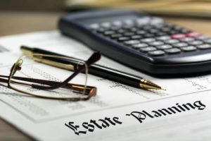 calculator, pen and glasses sitting on top of an estate planning document