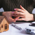 divorce - a woman removing her wedding ring, with toy car and house in front of her and a marriage contract