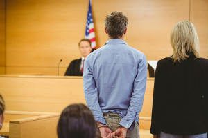 defendant in courtroom standing with handcuffs on