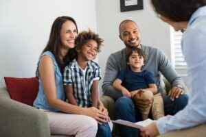happy family speaking to social worker about new adopted family member
