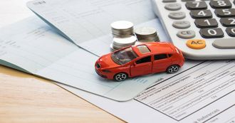 toy car and money on a paper representing car isnurance