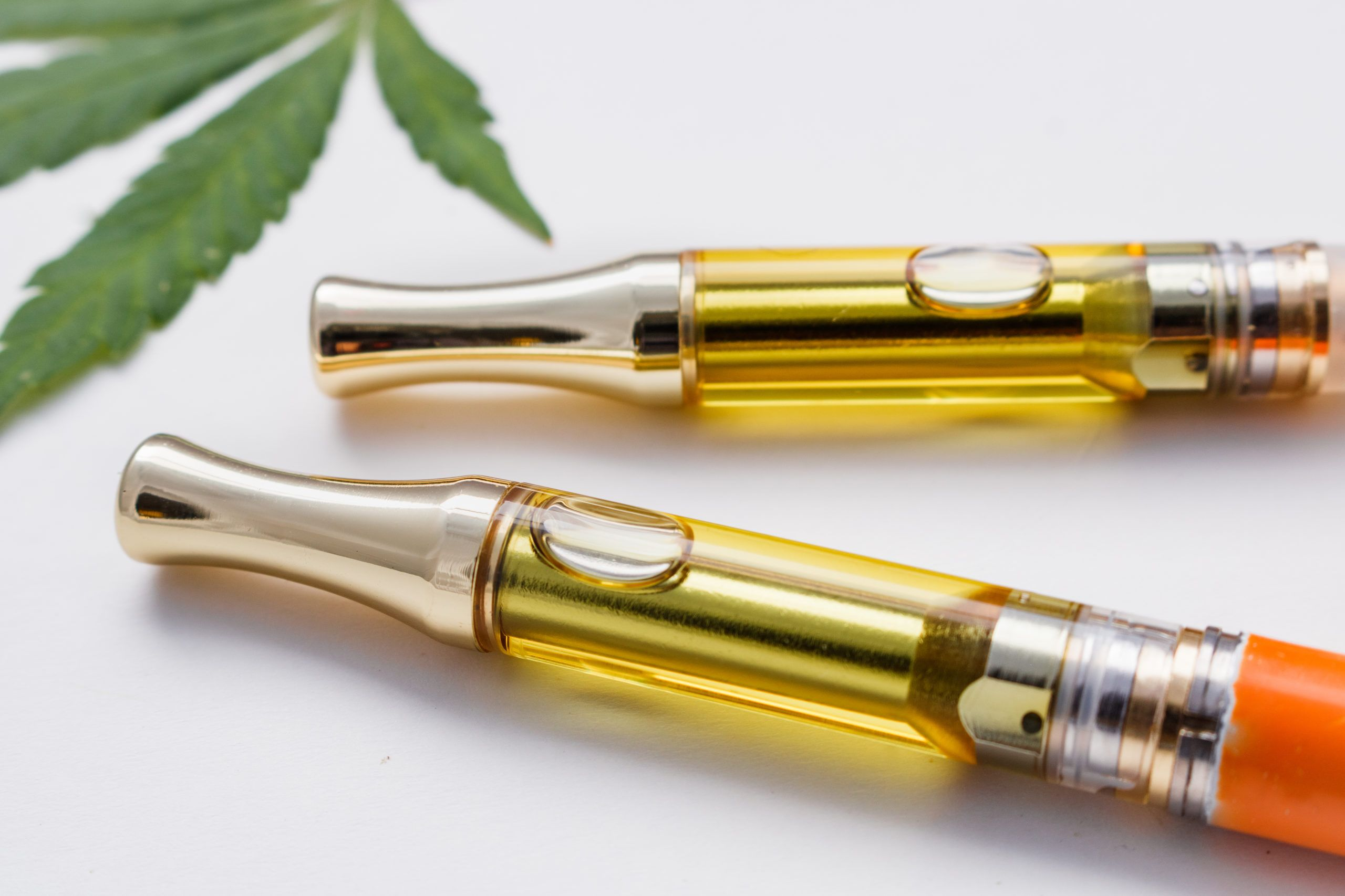 vape pens with a marijuana leaf in the background