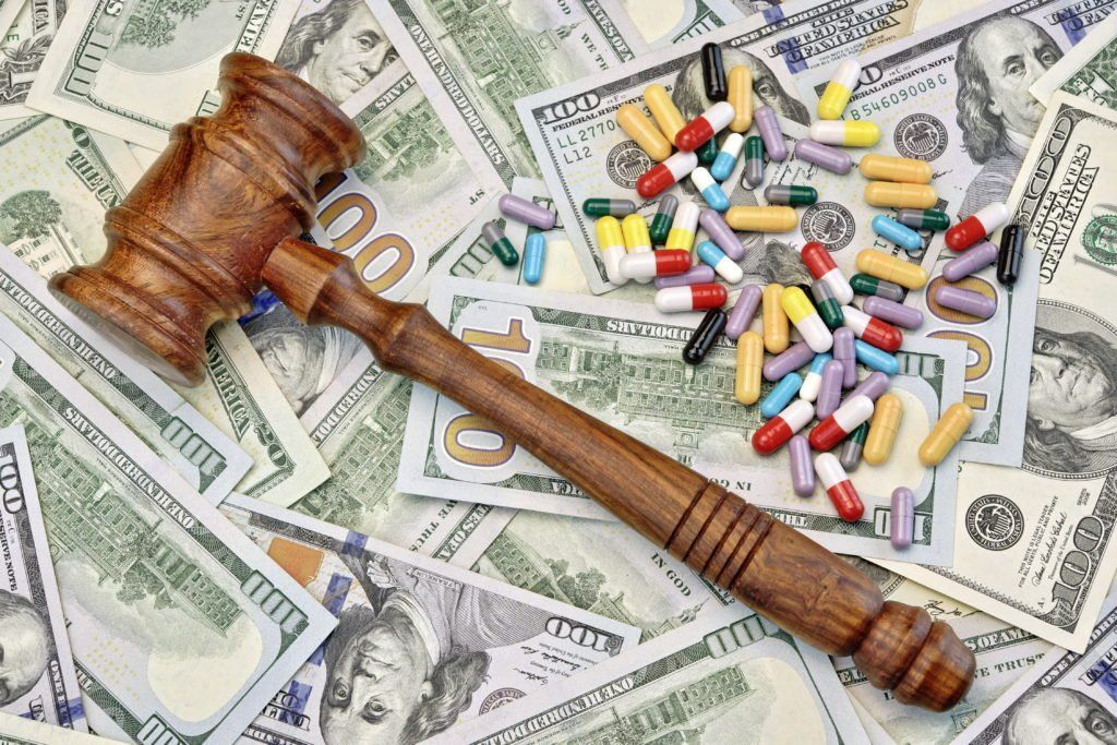Gavel and pills spread out over dollar bills to signify the expense in drug injury lawsuits.