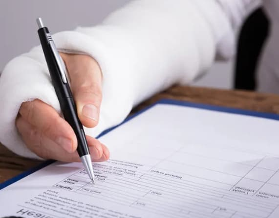 person with broken arm filling a legal form