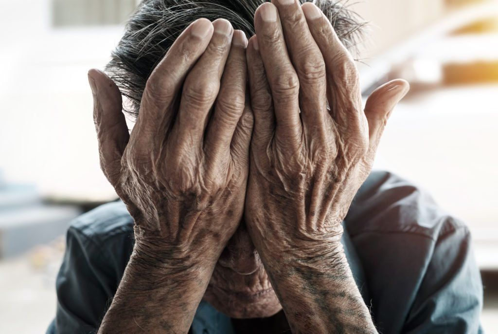 Elderly man puts palms to his head to represent his neglect in a nursing home