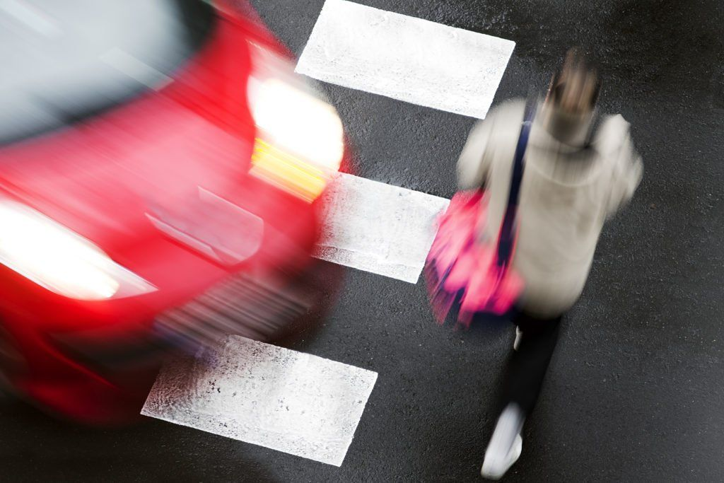 Woman crossing the road about to be hit by a car