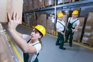Young afraid woman lifting heavy box in warehouse