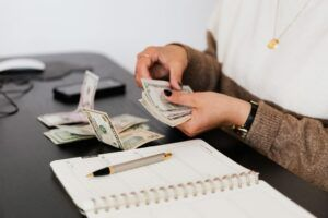 a woman counting dollar bill with pen documents