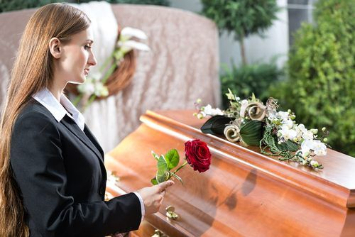 female laying flower on wrongful death victim's coffin.
