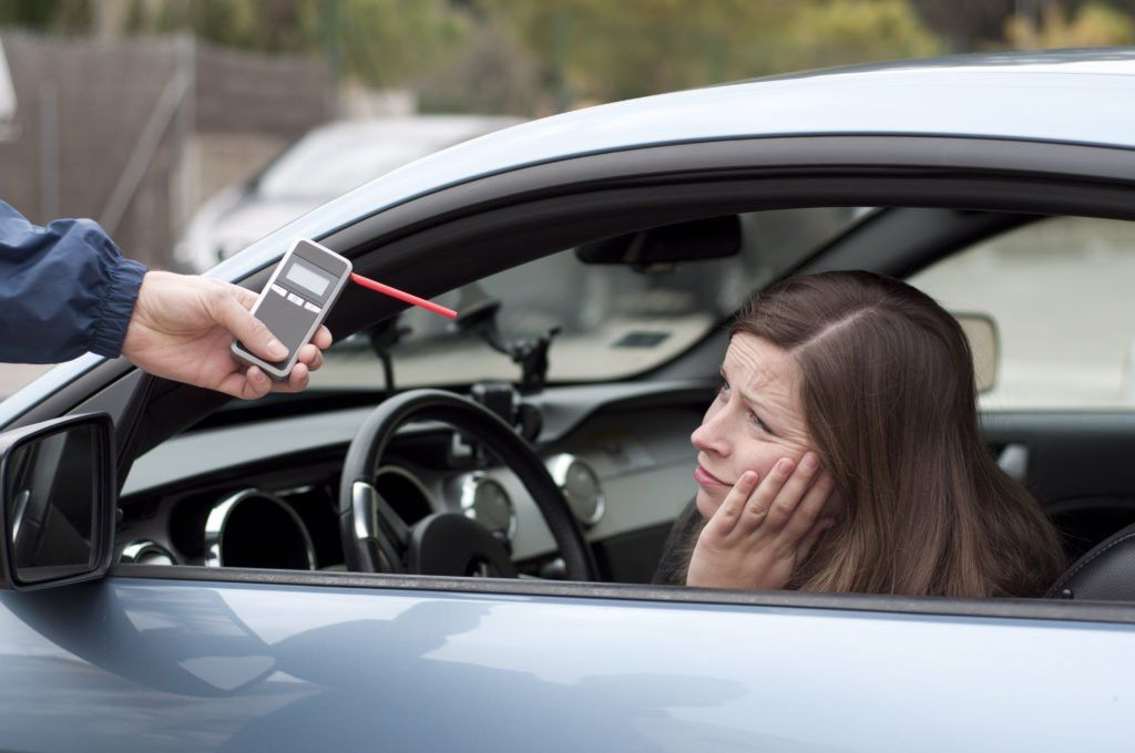 female being asked to blow in breathalyzer