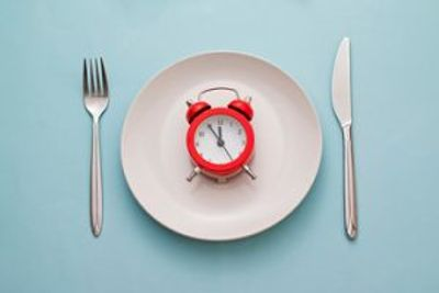 red alarm clock on a white plate