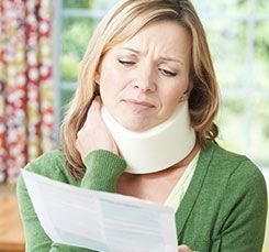 woman with neck brace on looking at paper