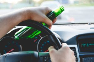 person with hands on wheel holding beer