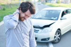 man holding neck in front of damaged vehicle