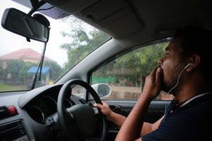 man wearing headphones while driving and covering mouth