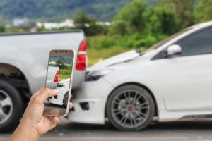 person taking picture of car accident