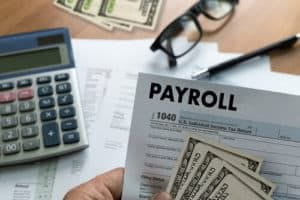 calculator, glasses, and payroll stub with money