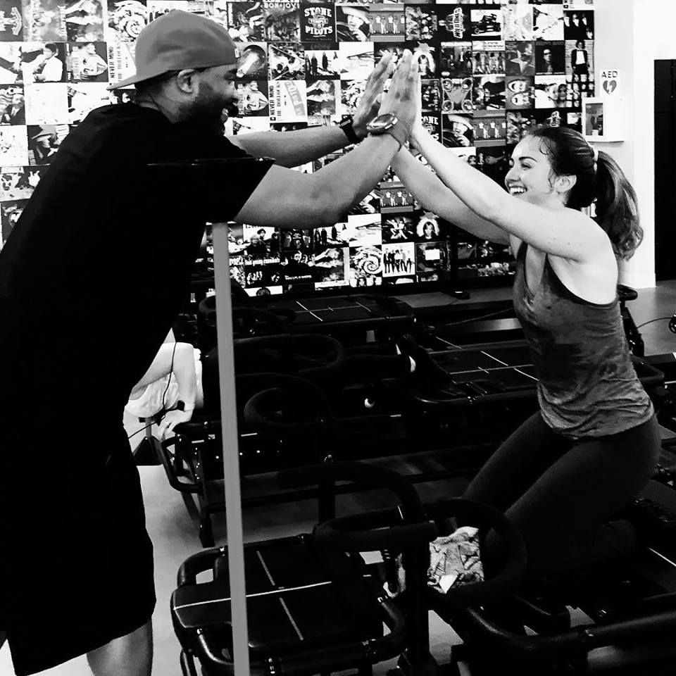 man and woman high fiving each other after workout