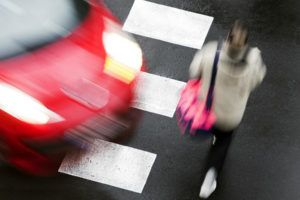 pedestrian crossing road in front of a fast moving car at crosswalk