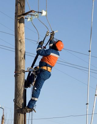 An electrical power line worker repairing a line