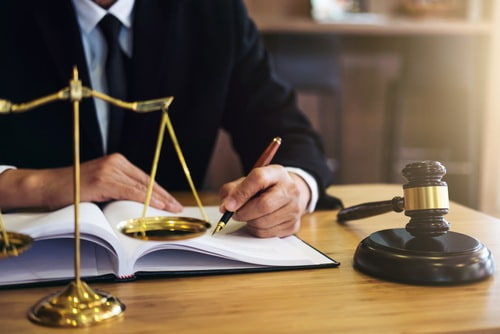 Lawyer sitting a desk with pen, paper and gavel