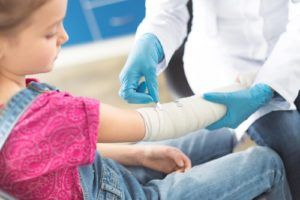 child having cast put on arm by a doctor