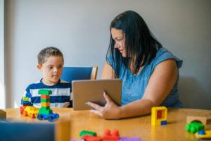 child that qualifies for social security disability playing with mom