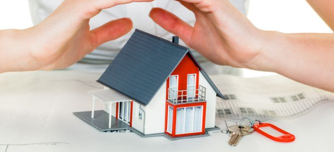 Womans hands over model of new home