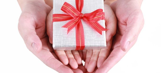 Hands holding a gift with a red bow.
