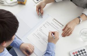 person signing construction documents with lawyer