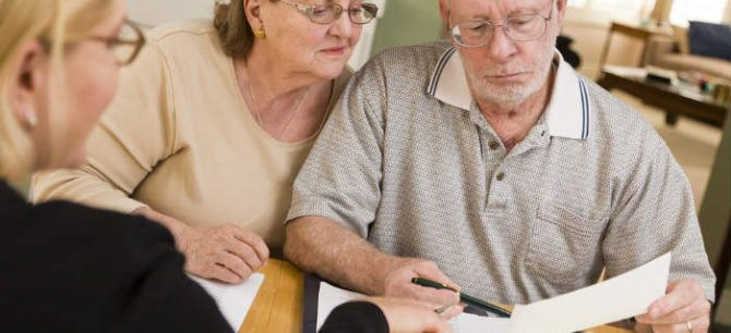Elderly couple looks over paperwork with attorney